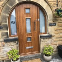 dark wood front door with three glass panes down the middle